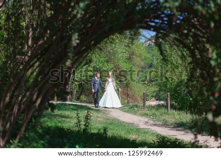 Beautiful bride and groom walk in the spring forest