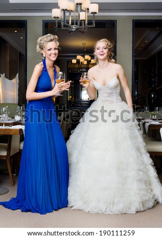 Beautiful Bride and her Bridesmaid with glasses of wine in a restaurant - stock photo