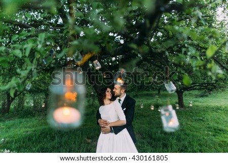 Beautiful bride and her loving groom in evening park holding each other under tree decorated with many lanterns - stock photo