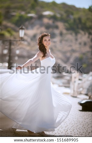Beautiful bride at wedding dress walking outdoors. Newlywed woman. Bride at marriage. Woman in wedding dress near sea. bride dance at wedding day. Girl in bridal dress on nature. happy wedding. series - stock photo