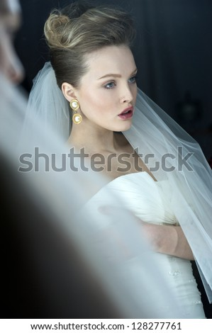 beautiful bride blond girl in white wedding dress with hairstyle and bright makeup looks in the mirror - stock photo