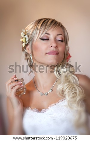 beautiful bride blond in white wedding dress with hairstyle and bright makeup. Happy sexy girl waiting for groom. Romantic lady in bridal dress and flowers in hair have final preparation for wedding