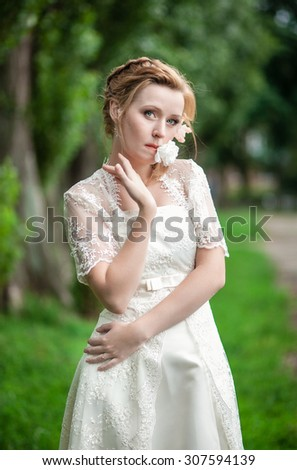 Beautiful bride defiantly holding a flower in his mouth and looks directly. wedding day