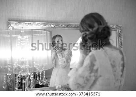 Beautiful bride  getting ready at hotel room. Bridal happy moments. Wedding picture in black and white.