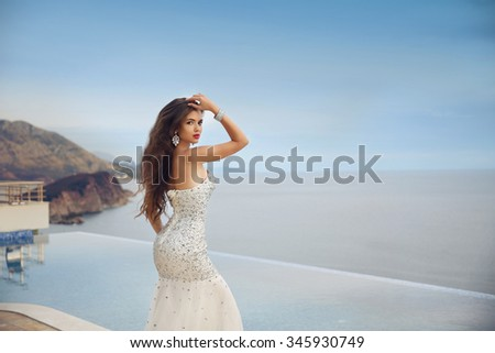 Beautiful bride girl in beaded wedding dress. Summer holiday fashion concept. Luxury resort woman posing by infinity swim pool over blue sky with sea. - stock photo