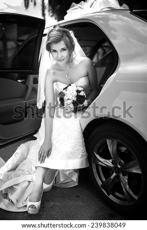 Beautiful bride goes out of the car near the road is ready for a new bright life, outdoor. Holding dress and bouquet in her hand. Long wedding dress, white veil. Black & white. Pretty young woman love - stock photo