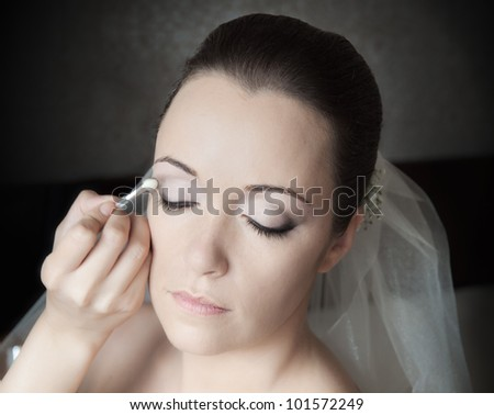 Beautiful bride having her make-up done by professional artist - stock photo