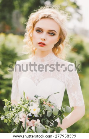 beautiful bride holding a wedding bouquet of flowers and posing on the lawn - stock photo