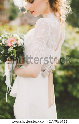 beautiful bride holding a wedding bouquet of flowers and posing on the lawn