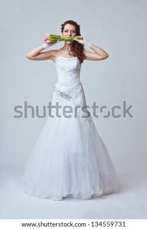 beautiful bride holding bouquet in her mouth - stock photo