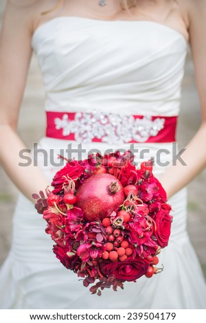 Beautiful bride holding bouquet outdoors close up - stock photo