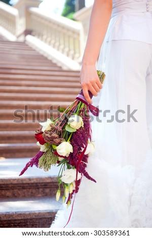 Beautiful bride holding wedding bouquet. Wedding dress . - stock photo