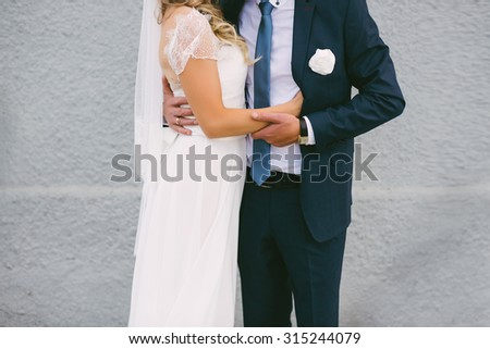 Beautiful bride hugs groom on a gray background, wedding, marriage, relationship, lifestyle - stock photo