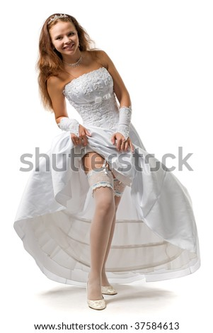 beautiful bride in a wedding dress shows a garter on a foot - stock photo