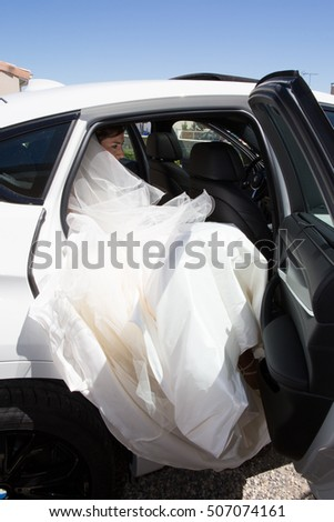 Beautiful bride in a white wedding car, happiness