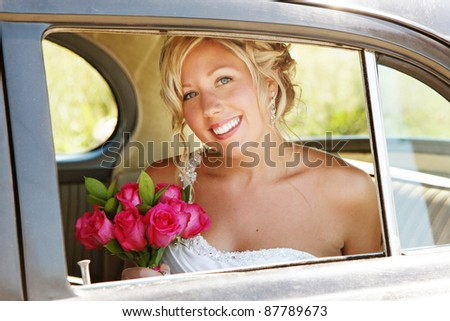 Beautiful Bride in Car on wedding day looking out Window - stock photo