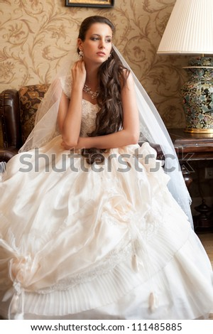 Beautiful bride in elegant wedding dress with long curly hair - stock photo