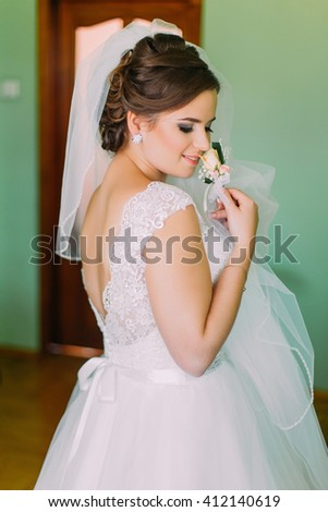 Beautiful bride in  lace wedding dress standing with his back to the camera.  - stock photo