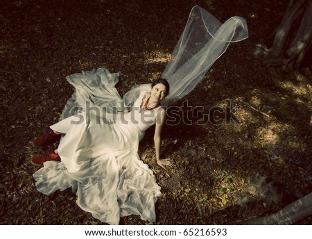 Beautiful bride in red boots in autumn forest