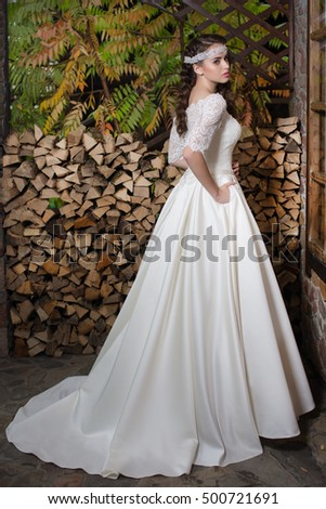 beautiful bride in satin wedding dress on a background of wood and autumn leaves
