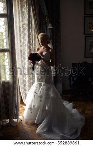 Beautiful bride in the luxury dress with a bouquet