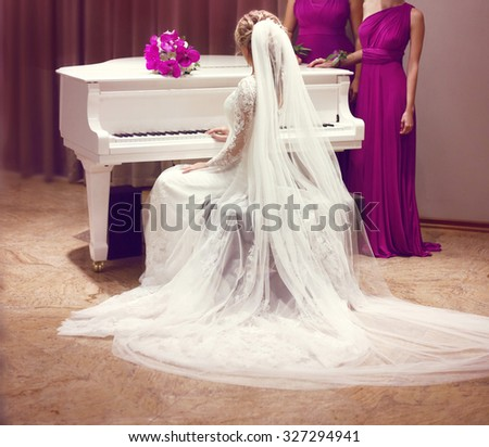 Beautiful bride in wedding dress and Bridesmaids. Fashion elegant girl with long veil sitting on white classic grand piano in interior. - stock photo