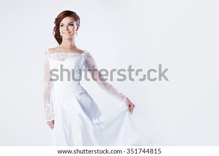 Beautiful bride in wedding dress, holds hem of dress and smiling, space for text on the right - stock photo