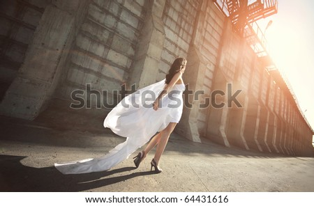 Beautiful bride in wedding dress walking down the street - stock photo