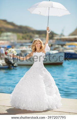 Beautiful bride in wedding dress with white umbrella posing over seafront, outdoor bridal portrait. Happy smiling fun young woman.  - stock photo