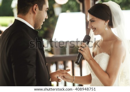Beautiful bride in white dress and handsome groom exchanging rings at wedding ceremony - stock photo