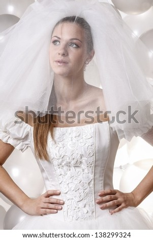 Beautiful bride in white dress in front of stunning decoration of thousands silver balloons