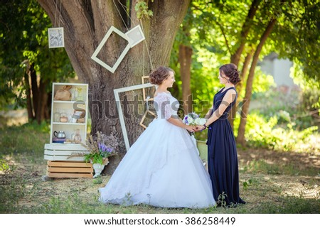 Beautiful bride in white dress with bridesmaid in the garden - stock photo
