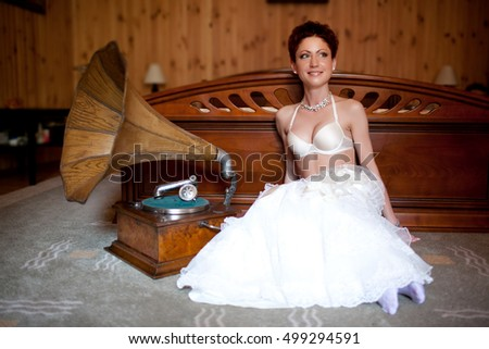Beautiful bride in white lingerie sits behind gramophone on the floor