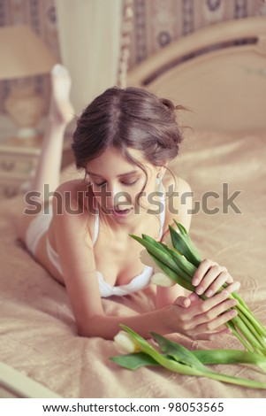 Beautiful bride in white lingerie with bouquet of white tulips lying on the bed in her bedroom - stock photo
