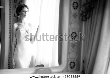 Beautiful bride in white wedding dress standing in her bedroom near the window - stock photo