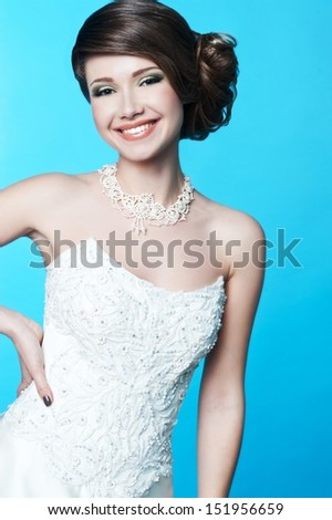 beautiful bride in white wedding dress with hairstyle and bright makeup - stock photo