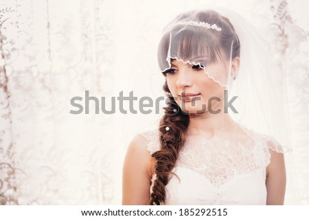 beautiful bride in white wedding dress with hairstyle and bright makeup. Happy sexy girl waiting for groom. Romantic lady in bridal dress and flowers in hair have final preparation for wedding - stock photo