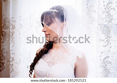beautiful bride in white wedding dress with hairstyle and bright makeup. Happy sexy girl waiting for groom. Romantic lady in bridal dress and flowers in hair have final preparation for wedding