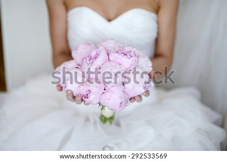 Beautiful bride is holding a wedding colorful bouquet. Beauty of colored flowers. Close-up bunch of florets. Bridal accessories. Female decoration for girl. Details for marriage and for married couple - stock photo