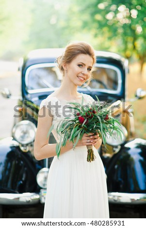 Beautiful bride is posing near black retro car