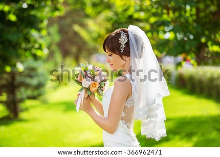 Beautiful bride is smelling wedding bouquet standing at green summer park background. - stock photo