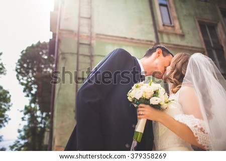 Beautiful bride kissing near the house