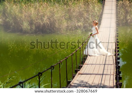 Beautiful bride looking at the river on suspension bridge