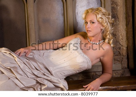 Beautiful bride lying on her side with blond curls - stock photo