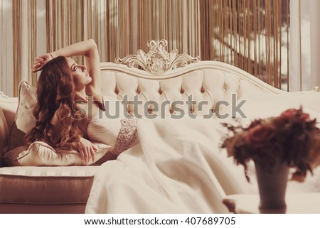 Beautiful bride lying on the sofa in a wedding dress in a luxury room. Portrait of relaxing woman with long curly hair in vintage style.