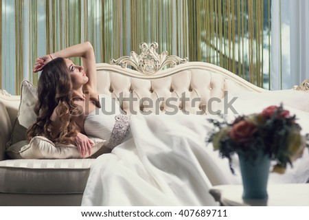 Beautiful bride lying on the sofa in a wedding dress in a luxury room. Portrait of relaxing woman with long curly hair.