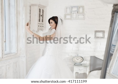 Beautiful bride making selfie by mobilephone. Side view. - stock photo