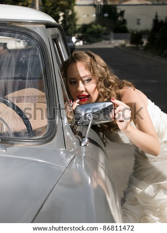 beautiful bride near the car - stock photo