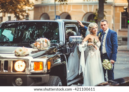 Beautiful bride next to a black car - stock photo