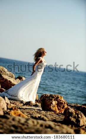 Beautiful bride on a rocky beach in a windy day. Romantic moment.  - stock photo